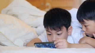 Asian child are playing on tablet, smiling, laying on bed.