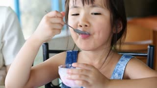 Asian child eating an ice creme in relax time .
