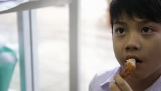Asian child eating chicken wing