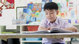Asian child in student uniform reading and writing to do homework of the school .