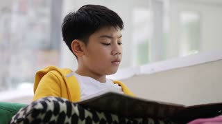Asian child is reading and doing homework of the school .