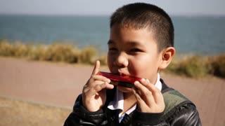 Asian child playing harmonica, mouth organ
