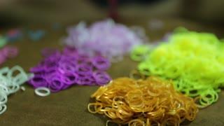 Asian child spins rubber band loom bracelets