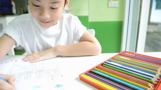 Asian child with color pencil set in box, painting in a book to do homework of the school