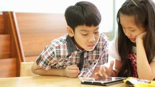 Asian children using a digital tablet together .
