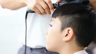 Asian cute boy make in a hairdressing salon ,unidentified hair stylistic