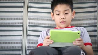 Asian cute boy playing tablet pc in the park at bright summer day