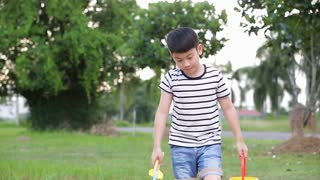 Asian cute boy playing with toys in garden,dolly camera