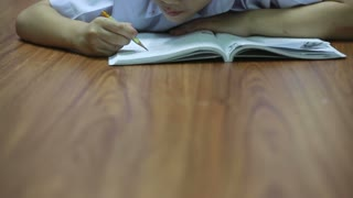 Asian cute boy reads the book on the floor at home.