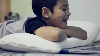Asian cute boy watching and talking on laptop computer.