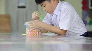 Asian cute boy with play plastic toys at school, Art hours.