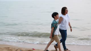 Asian family mother and son walking and looking sunset with sea background
