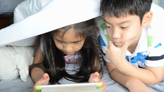 Asian girl and boy play on tablet on the bed