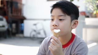 Asian kid enjoy delicious ice cream cone during the summer.