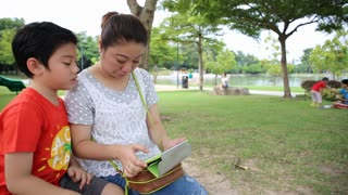 Asian mom with her children playing tablet computer in the park .