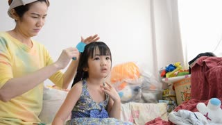 Asian mother combing her cute daughter's hair.
