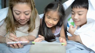 Asian mother with your son and daughter play on tablet on the bed .