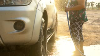 Asian senior female washing Family car with water tube,Slow motion shoot with ,120 Fps By Sony A6300 .