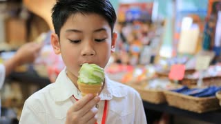 Asian siblings enjoying with ice cream cone in gift shop