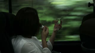 Asian woman applying beauty make up in the bus,moving