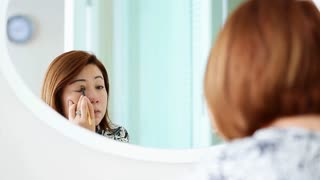 Asian woman applying makeup and looking at mirror in bedroom.