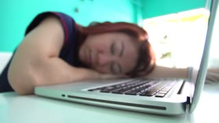 Asian woman falling asleep behind laptop.