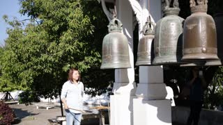 Asian woman knocking the bells for worship at temple ,thailand