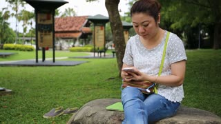 Asian woman using mobile phone in the park .