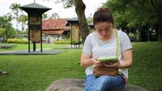 Asian woman using tablet pc in the park .