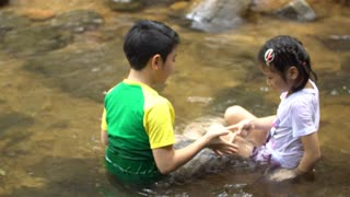 Boys and girls are playing Rock Paper Scissors in the river