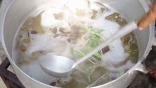 Chicken soup boiling in a kitchen pot .