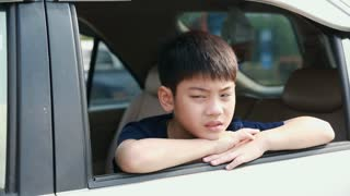 Child Traveling by Car, Asian boy Looking out of Window During stop, Trip in city