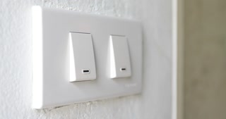 Close up clips of Man's had turning light on and off, hand groping wall to find light switch, shot in 4K video