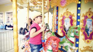 Close up of asian child riding carousel at carnival