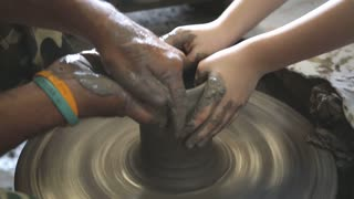 Close up of hands working clay on potter's wheel and little hand learning .
