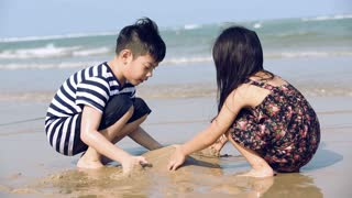 Closeup Of asian Boy And Girl Hard At Work, Building Castles In The Sand beach