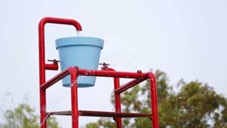 Colorful bucket splash in aqua park