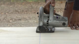 Construction worker cutting wood planks with circular electric saw outdoors at location building.