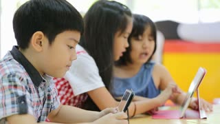 Group of Little Asian child playing together with a computer tablet .