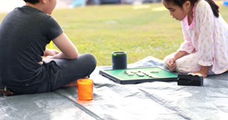 Happy asian boy and girl playing board game in camping area
