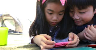 Happy asian boy and girl playing smart phone and tablet in camping area