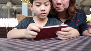 Happy asian boy and his mom playing games on smart phone