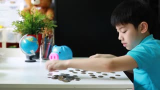 Happy Asian boy counting coins from piggy bank and put together