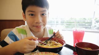 Happy asian boy eating japanese lunch set ,and looking camera .