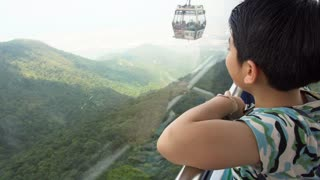 Happy asian boy in cable car ,looking nature hill