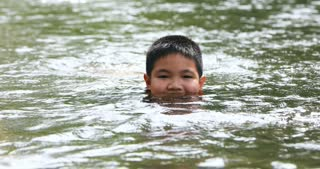 Happy asian boy playing waterfall in Thailand