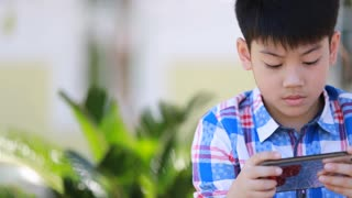 Happy asian boy sitting and using smart cell phone in park