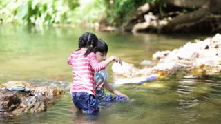 Happy asian brother and sister are playing in water stream