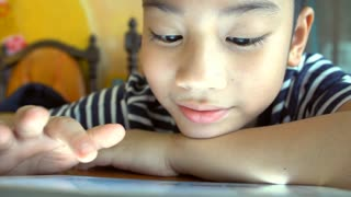 Happy Asian Child watching and play on tablet computer