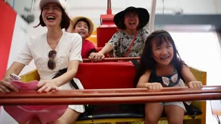 Happy Asian child with mother playing speed boat in amusement park